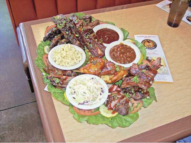 One of the best restaurant values in the SCV is the BBQ Family Value Meal from Smok'n Joe's BBQ Pit in Canyon Country. Priced from $55 to $155 the three options include a variety of barbecue meats and sides. The platter above ($55) serves four to six and includes  Texas giant beef ribs, baby back pork ribs, a whole chicken, tri-tip or brisket, garlic bread and four side orders.