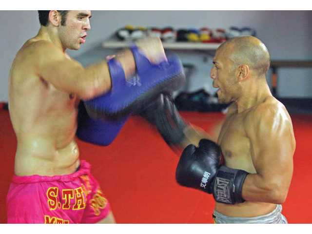 Local muay thai fighters Francisco Funicello, left, and Hector Godoy spar on Wednesday at World Muay Thai Gym in Santa Clarita. Both men have fights scheduled for Saturday.