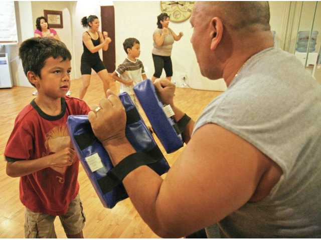 Seven-year-old Fernando Perez works out with Pastor Gilbert Burns at the Santa Clarita Christian Center on Tuesday.