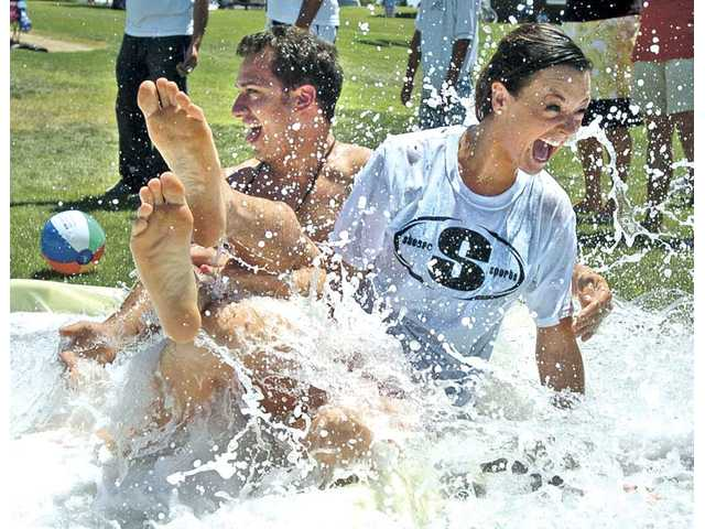 "Holly Durst from the ABC TV show, ""The Bachelorette,"" and Robby Descant from ""The Bachelor"" collide at the bottom of a 50-foot Slip 'N Slide during a Project Parachute fundraiser hosted by Stesso Sports on Saturday."