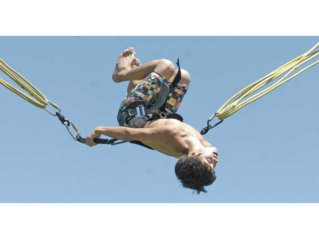 Koby Garcia, 11, of Valencia, bounces upside down on the Acro Flight bungee jump at Bridgeport Park in Valencia on Saturday during an event hosted by Stesso Sports that benefited Project Parachute, a nonprofit organization that aims to help single parents through various programs.