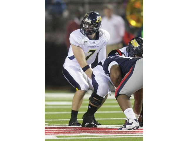 Valencia High graduate and Northern Arizona quarterback Michael Herrick takes a snap against Ole Miss last season.