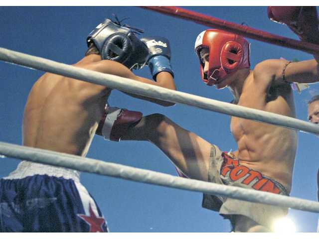 Saugus High School student and muay thai fighter Vito Funicello, right, throws a kick at opponent Erick Gonzales during their bout at the World Muay Thai Council World Championships on Saturday night at Saugus Speedway.