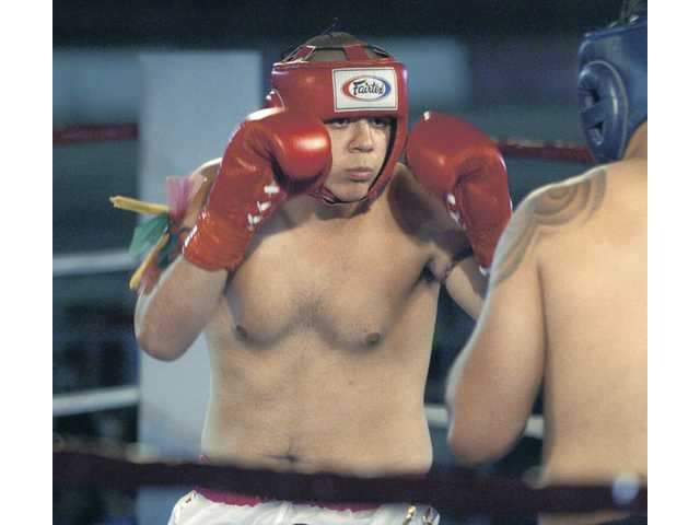 Golden Valley High School student and muay thai fighter Anthony Lahn, left, competes against Ronald Cruz at the World Muay Thai Council World Championships on Saturday night at Saugus Speedway. Lahn lost the bout.
