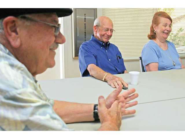 From left to right, John Stam, Jack Freed and his wife, Ginger, talk about the news at the Santa Clarita Valley Senior Center in Newhall during a recent current-events discussion group meeting.