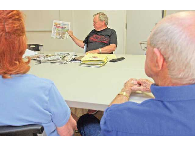 William Stehle holds up a copy of The Signal while he talks about headlines in the news during a recent meeting of a current-events discussion group at the Santa Clarita Valley Senior Center.