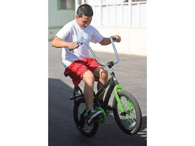 Dennys Cardona, 12, rides Doug Fraser's patented bicycle design, which places the seat on top of the rear wheel.