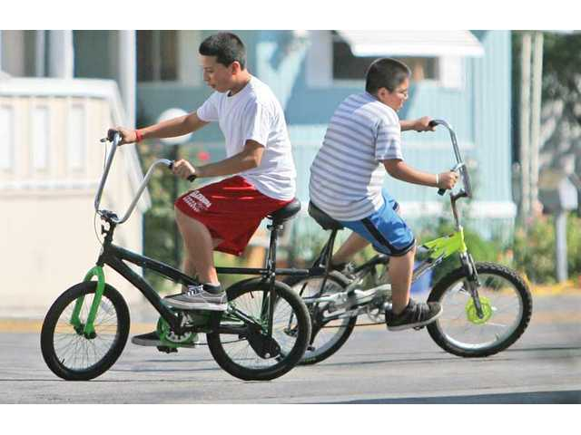 From left, Dennys Cardona, 12, and Jonathan Galan, 11, enjoy a ride on local inventor Doug Fraser's patented bicycle design, which places the seat on the rear wheel.