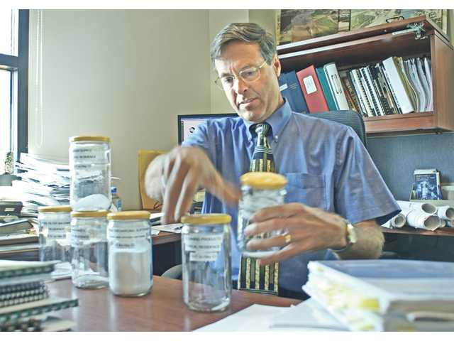 Bert J. Rapp, Fillmore's Public Works Department director, displays mason jars containing daily discharge of chloride from several different household sources.