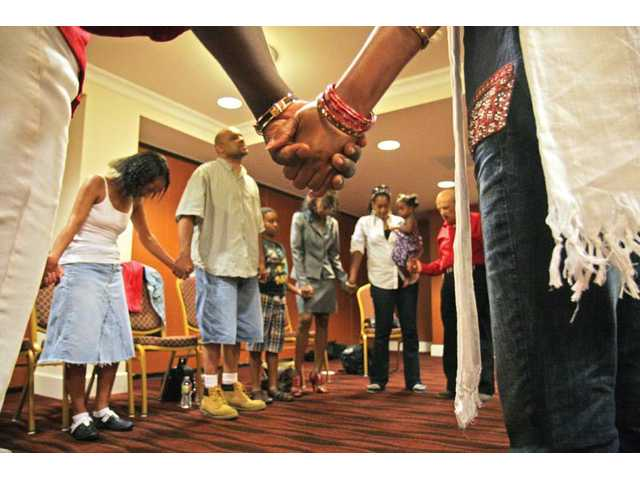 Members of the Fresh Fire Intercession Ministry pray during their congregation's weekly meeting, which takes place Mondays at 11:30 a.m. at the Embassy Suites in Valencia.