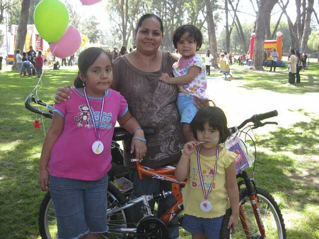 A young girl and her family show off the bike she won through the free raffle at the 2009 Day for Kids, sponsored by the City and the Boys &  Girls Club of Santa Clarita Valley.