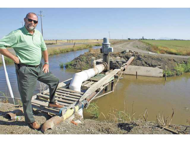 Royce W. Cunningham, city engineer for Dixon, stops by one of the town's many irrigation ditches which is about 30 feet from one of five wells he uses to monitor chloride levels in water.