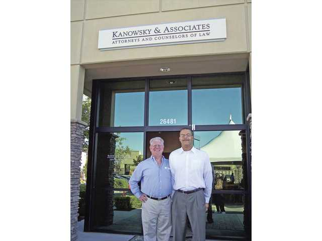 Attorneys Carl Kanowsky, left, and Jeff Lasley stand under the sign for the Kanowsky and Associates law firm that held a grand-opening celebration on Aug. 19 for its relocation to the Summit Point office park in Santa Clarita.