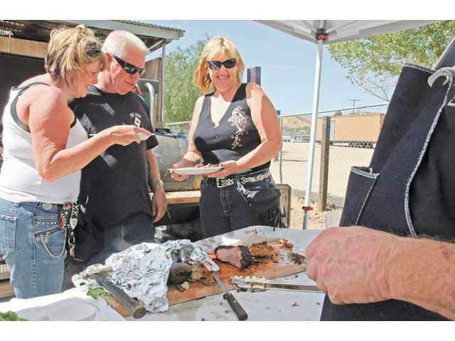 Rodger McIndoe, center, is congratulated along with Todd Towne, far right, by Vicki Zellner, left, and Sue Reffner for winning first place at the BBQ Cook Off to benefit the VFW Post 6885, in Canyon Country on Saturday afternoon. Towne and McIndoe received a plaque for having cooked tri tip, pork butt, chicken, pork ribs, jalapeños, corn, onions and tortillas. Money collected at the event went toward the remodeling of the posts' kitchen.