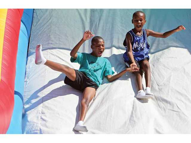 Sam and Solomon Strader slide down an inflatable slide at the second annual YOUth Sports Festival at Central Park. The event offered free games and sports from 10 a.m. to 2:30 p.m.