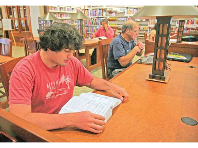 Eighteen-year-old Brandon Faber reads about computers at the Calabasas Library on Thursday.