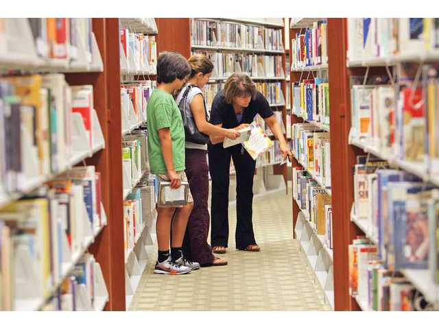 Librarian Marcy Bowen helps Hamideh Golestaneh and her 12-year-old son Shayan Zianour at the Calabasas Library on Thursday afternoon. The Santa Clarita City Council is expected tonight to approve seceding from the Los Angeles County Library System and entering into a contract with a private library management firm to run the city's three libraries.