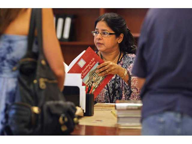 Library Technical Services Coordinator Suchandra Ghosh, helps a customer checkout books at the Calabasas City Library on Thursday afternoon.