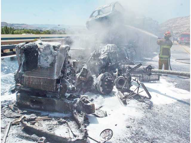 The picture above shows the charred remains of an injury crash on Highway 14 north of Sand Canyon Road, which shut down traffic in both directions at around 1 p.m. Wednesday in triple-digit heat. Authorities reported that a big rig carrying several cars collided into a Caltrans truck that was parked on the shoulder at 1:15 p.m. The big rig's driver was transported to Henry Mayo Newhall Memorial Hospital with moderate injuries.