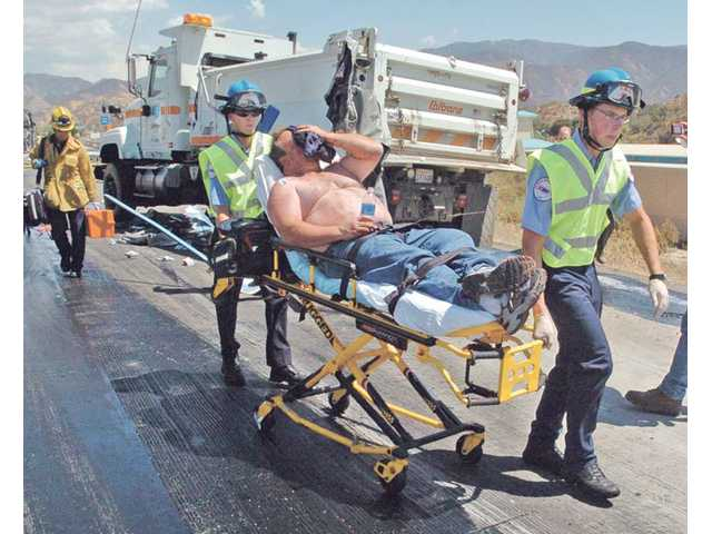 The driver of a big rig is transported to Henry Mayo Newhall Memorial Hospital after a collision on Highway 14 north of the Sand Canyon Road off-ramp Wednesday.