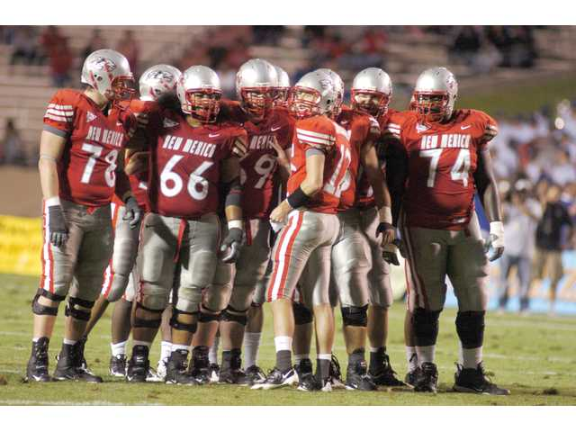 Hart graduate B.R. Holbrook, center, talks to his team in a huddle last season. Holbrook has been named the University of New Mexico's starting quarterback.