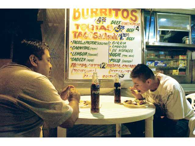 Oregon trucker Sam Maldonaldo, left, and son Adam, 14, stop for dinner at 2 a.m. on Friday at the El Grullense Taco wagon in Castaic.  They were heading to Riverside to pick up a load of new tires they will take to Canada.