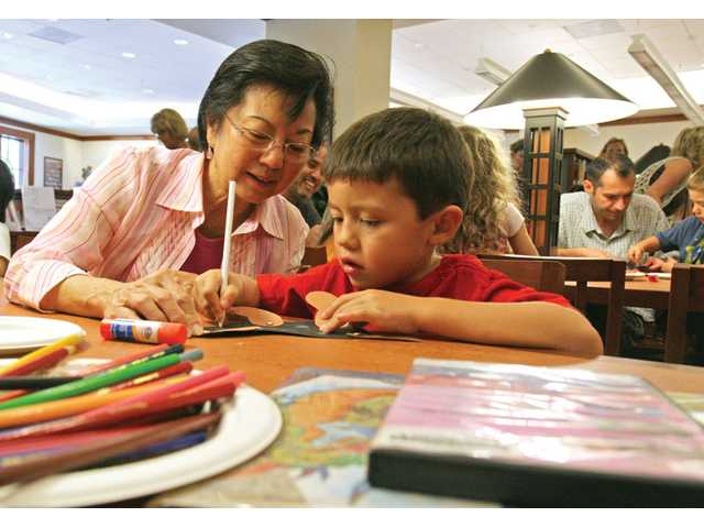 Etta Siu and her 5-year-old grandson Kyler Rumack work on an art project during Pumpkin Patch with Craft Storytime, a weekly children's program at the Calabasas Library. The Santa Clarita City Council voted on Tuesday to take over the three libraries within city limits, withdrawing them from the current Los Angeles County library system.