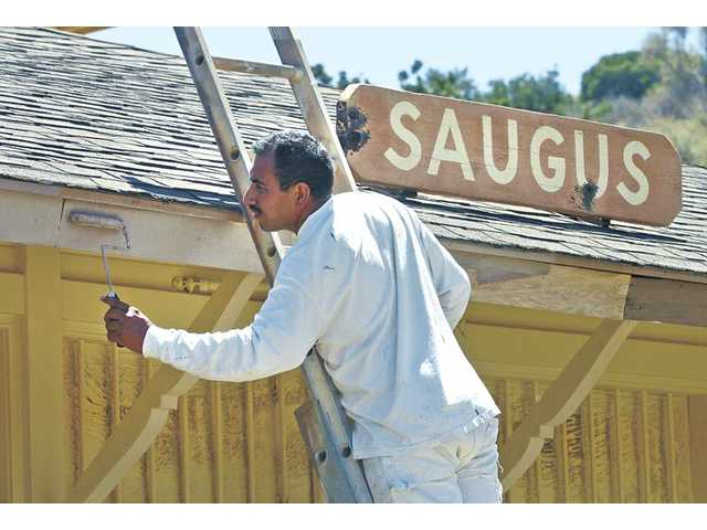 Jorge Peralta, of De Mac Painting & Coating Inc. in Santa Clarita, paints a second coat of primer on the trim of the Saugus Train Station at the Heritage Junction Historical Park. The painting and recent renovation was made possible by two grants from the Newhall Family Foundation.