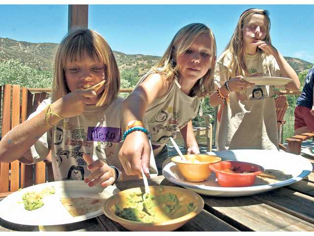 The Painted Turtle campers Alexa Sutherland, 12, Caitlin Ryan, 12, and Mikayla Minnig, 12, enjoy quesadillas at lunchtime. The trio calls themselves the Mickey D Group and became fast friends while camping at the nonprofit's Lake Hughes facility.