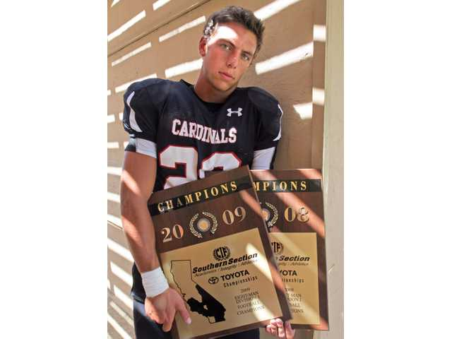 Santa Clarita Christian senior wide receiver and linebacker Ryan Espinosa, the team's captain, holds the plaques honoring the school's consecutive CIF-Southern Section Division I 8-Man Football championships from the past two years.