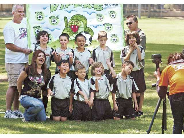 AYSO 46 Vipers team members clown for the camera at the Saugus American Youth Soccer Organization 46 opening day carnival and picture day fundraiser in Newhall on Saturday.