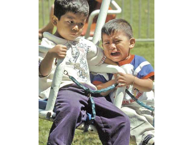 Alex Cuervo, 4, left, and brother Brandon, 2, of Newhall, ride the two-seat swing ride.