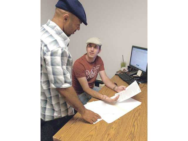 Veteran Affairs Program Manager Renard Thomas, left, and veteran education benefits adviser Josh Eggman discuss the application form of a vet who did not show up for a recent appointment at the Adult Re-entry Veterans Center at College of the Canyons.