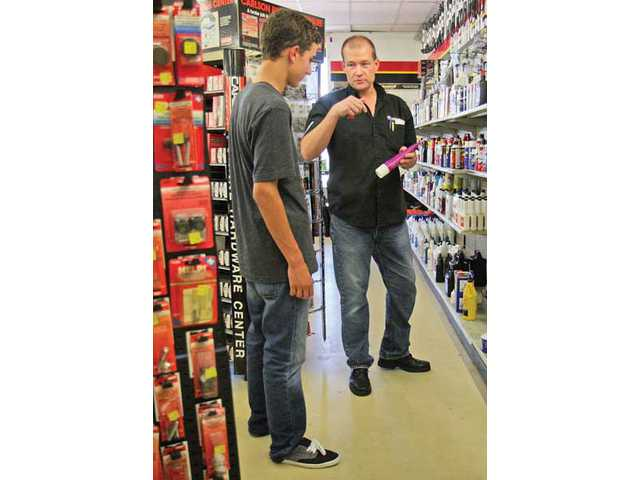 Powell helps out customer Paul Trentini, of Saugus, look for lithium grease for his sunroof on Monday afternoon. The store has served the SCV since 1972.