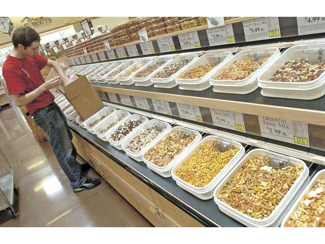 Clerk Timothy Wilson stocks the bulk-food section last Thursday in preparation of the opening of Sprouts Farmers Market in Valencia. Sprouts opens today.
