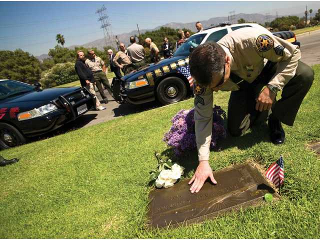 """Ventura County Sheriff's Detective Garo Kuredjian pauses next to the grave of his brother Hagop """"Jake"""" Kuredjian during a memorial service at Forest Lawn Memorial Park in Hollywood Hills on Tuesday."""
