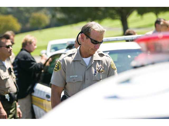 Sheriff's Deputy Robert Wagner looks at a sheriff's cruiser detailed with the names of 477 Sheriff's Department personnel killed in the line of duty in California since 1850.