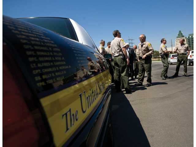 Sheriff's deputies talk next to a police cruiser detailed with the names of more than 1,300 U.S. law enforcement personnel killed since Sept. 11, 2001, Tuesday at Forest Lawn Memorial Park in Hollywood Hills.
