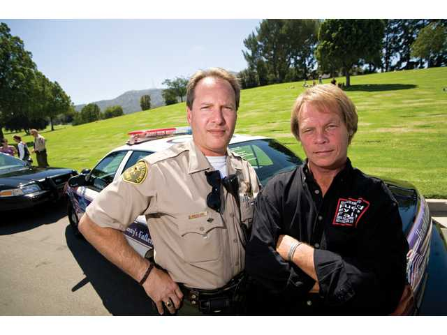 Sheriff's Deputy Mike Ascolese, left, and Kevyn Major Howard stand by one of two squad cars customized by Fueled by the Fallen, Tuesday at Forest Lawn Memorial Park in Hollywood Hills. The nonprofit organization, started by Howard, turns vehicles into mobile memorials for law officers and troops killed in the line of duty.