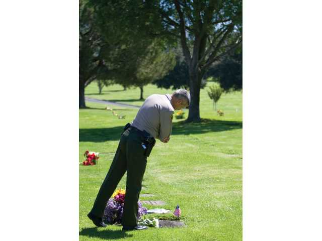 """Sheriff's Deputy Dennis Schwartz stands over the grave of Deputy Hagop """"Jake"""" Kuredjian, Tuesday at Forest Lawn Memorial Park in Hollywood Hills. Kuredjian was killed during a shootout in Stevenson Ranch on Aug. 31, 2001."""
