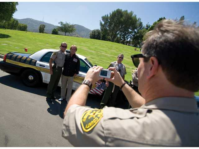Sheriff's Deputy Mike Ascolese takes a photo of Deputy Robert Wagner, left, and Kevyn Major Howard, next to a police cruiser bearing the names of 1,300-plus U.S. law officers killed in the line of duty since Sept. 11, 2001, Tuesday at Forest Lawn Memorial Park in Hollywood Hills.