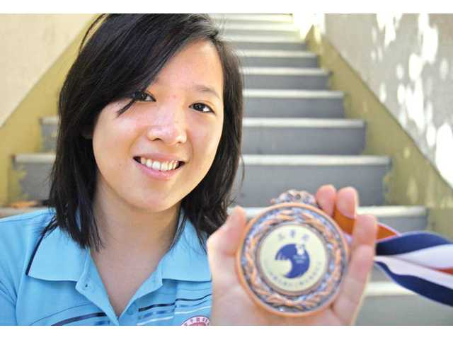 Adisa Kruayatidee, 17, of Stevenson Ranch, shows the bronze medal she recently earned during an international math competition in China.