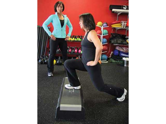 Rachel Cosgrove watches as Holly Song performs a lunge at Results Fitness.