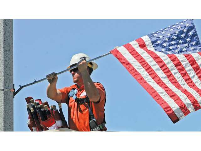 City employee Dan March places a flag on a lightpost on Soledad Canyon Road near Ironstone Drive in Canyon Country on Thursday in preparation for Labor Day weekend. As families gear up for out-of-town travel, The Signal looks at how gas prices and the economy could affect the weekend-traffic picture.