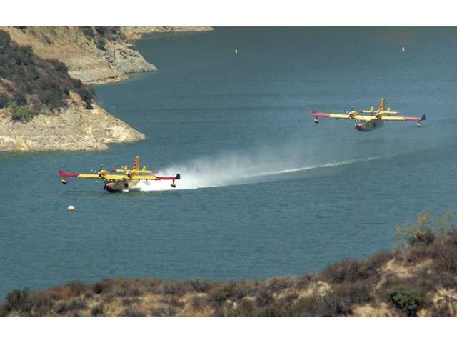 Two CL-415 SuperScoopers fire-fighting aircraft perform training exercises Wednesday at Castaic Lake, where the planes are picking up 1,600 gallons of water.