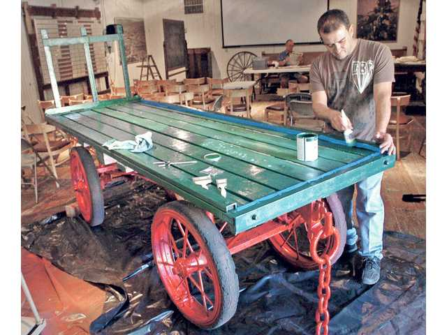 Volunteer Khaled Zakher paints the hardwood bed of a Railway Express Agency express wagon that dates back to the 1920s at Saugus Train Station at Heritage Junction and Museum at William S. Hart Park in Newhall on Aug. 16.
