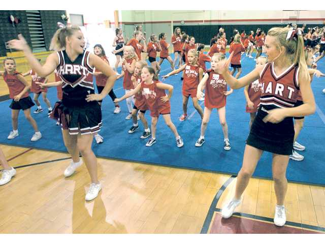 Hart High School cheerleaders Sammy Spiegel, 16, left, and Chloe Calvwell, 14, lead a group of 5- to 7-year-olds at Hart Spirit Day cheerleader camp at Hart High School on Aug.  28.