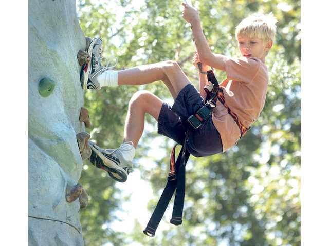 Cameron Labrie, 10, of Saugus, scales down a climbing wall at Saugus AYSO 46 opening-day carnival and picture-day fundraiser at Newhall Park on Aug. 28.