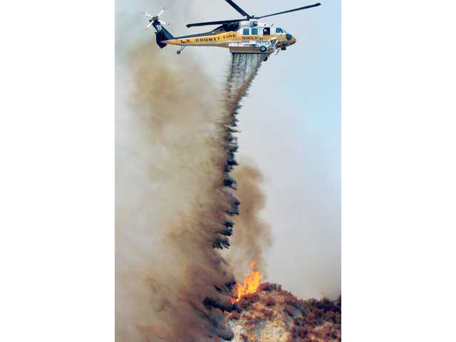 A Los Angeles County Firehawk water-dropping helicopter makes a drop on a brush fire that burned up a steep ridge near Pico Canyon Road and Southern Oaks Drive in Stevenson Ranch on Tuesday.