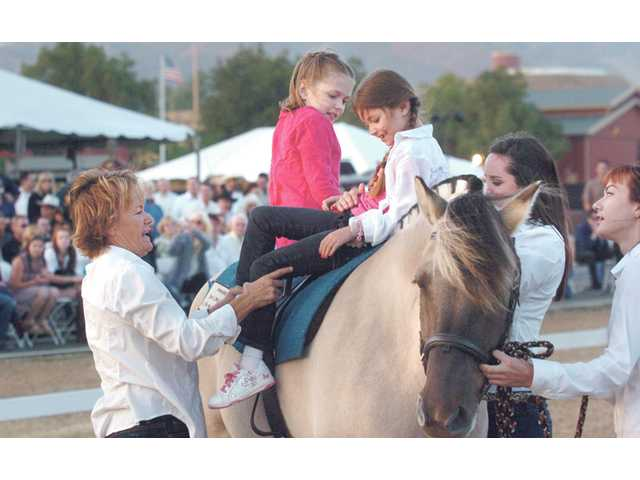 Becky Graham, left, helps Emma Clift, 8, and Katie Kimes, 7, maneuver into position as they demonstrate their riding skills on a horse at Heart of the West on Aug. 28.